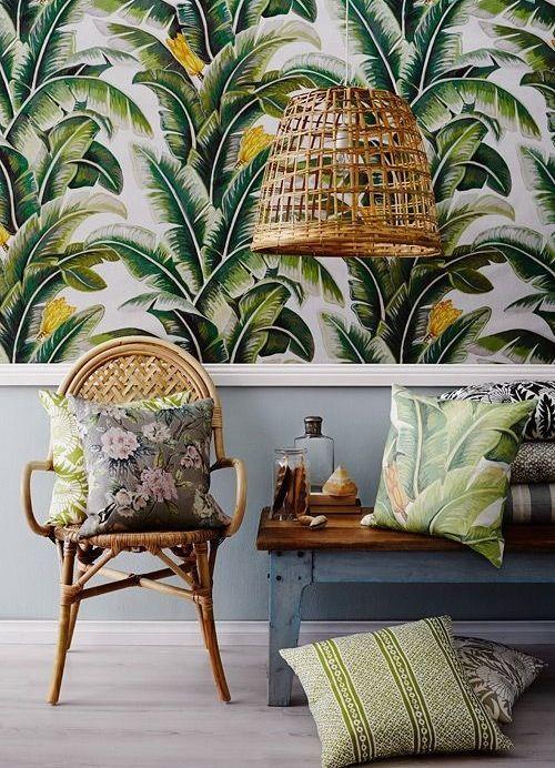 Tropical beach interior with cane chair palm print wallpaper & cushions & cane pendant light