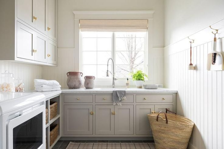 White and gray laundry room designed with white beadboard trim, gray shaker cabinets, and antique vintage brass latch hardware. #graylaundryrooms White and gray laundry room designed with white beadboard trim, gray shaker cabinets, and antique vintage brass latch hardware. #graylaundryrooms