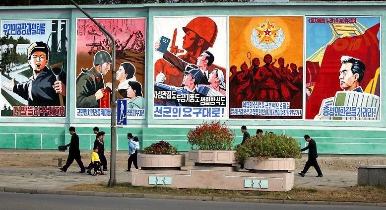Gezeichnete Parolen, die die Überlegenheit des eigenen Systems und des eigenen Volks beschwören, sollen die rund 25 Millionen Nordkoreaner auf Parteilinie halten.