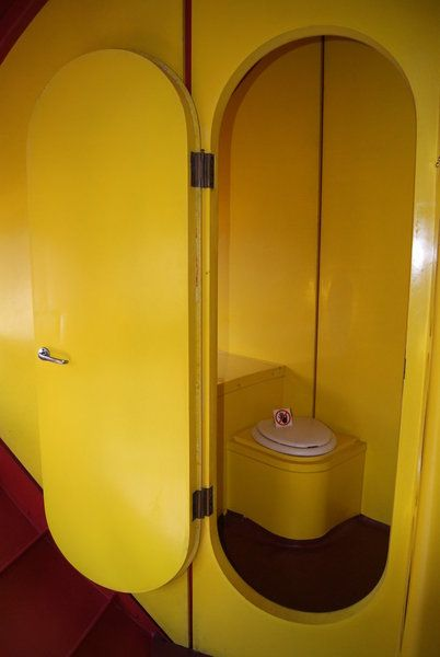 toilet inside a Futuro House; does the little sign mean don't reach into the toilet? Who does that?