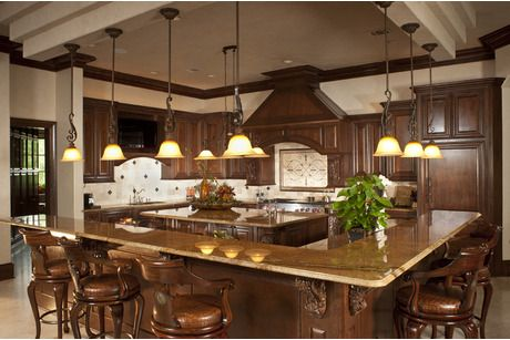 Hanging lights and an L-shaped counter define this elegant kitchen. A build-on-your-lot home from Design Tech in San Antonio, TX.