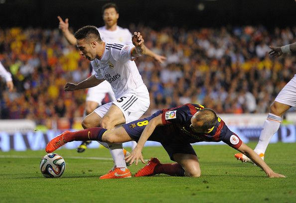 Andres Iniesta (R) of Barcelona is tackled by Daniel Carvajal of Real Madrid during the Copa del Rey Final between Real Madrid and Barcelona at Estadio Mestalla on April 16, 2014 in Valencia, Spain.