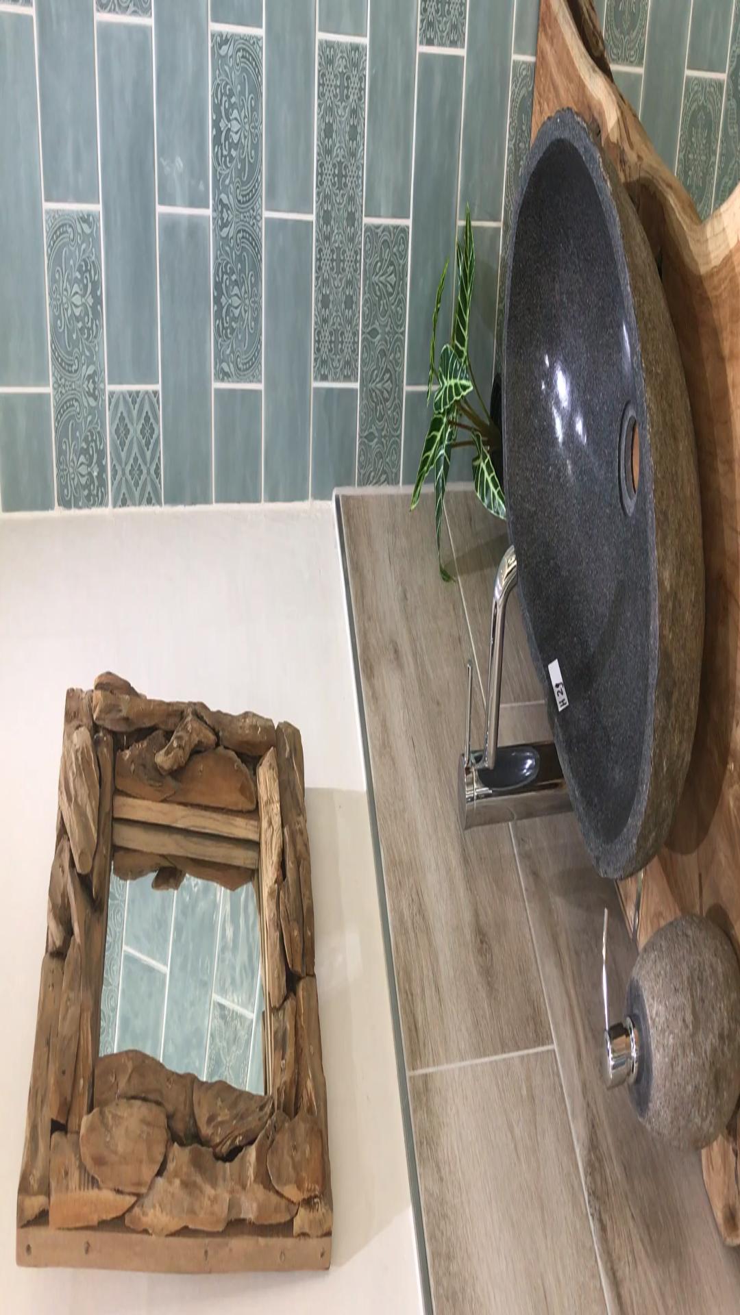 Retrostyle im Gäste WC Natursteinwaschbecken auf Holzplatten liegen im Trend dazu die passenden Metrofliesen und Dekoration von einem Holzspiegel und Hocker