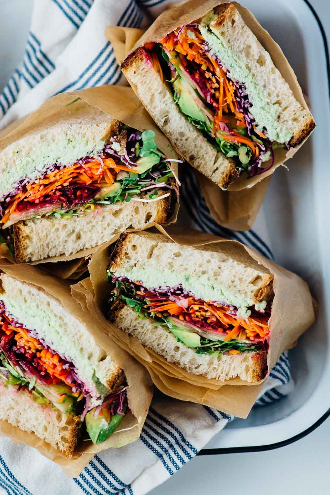 This ultimate rainbow veggie sandwich is loaded with fresh veggies and topped off with a garlicky basil almond ricotta. Delicious!