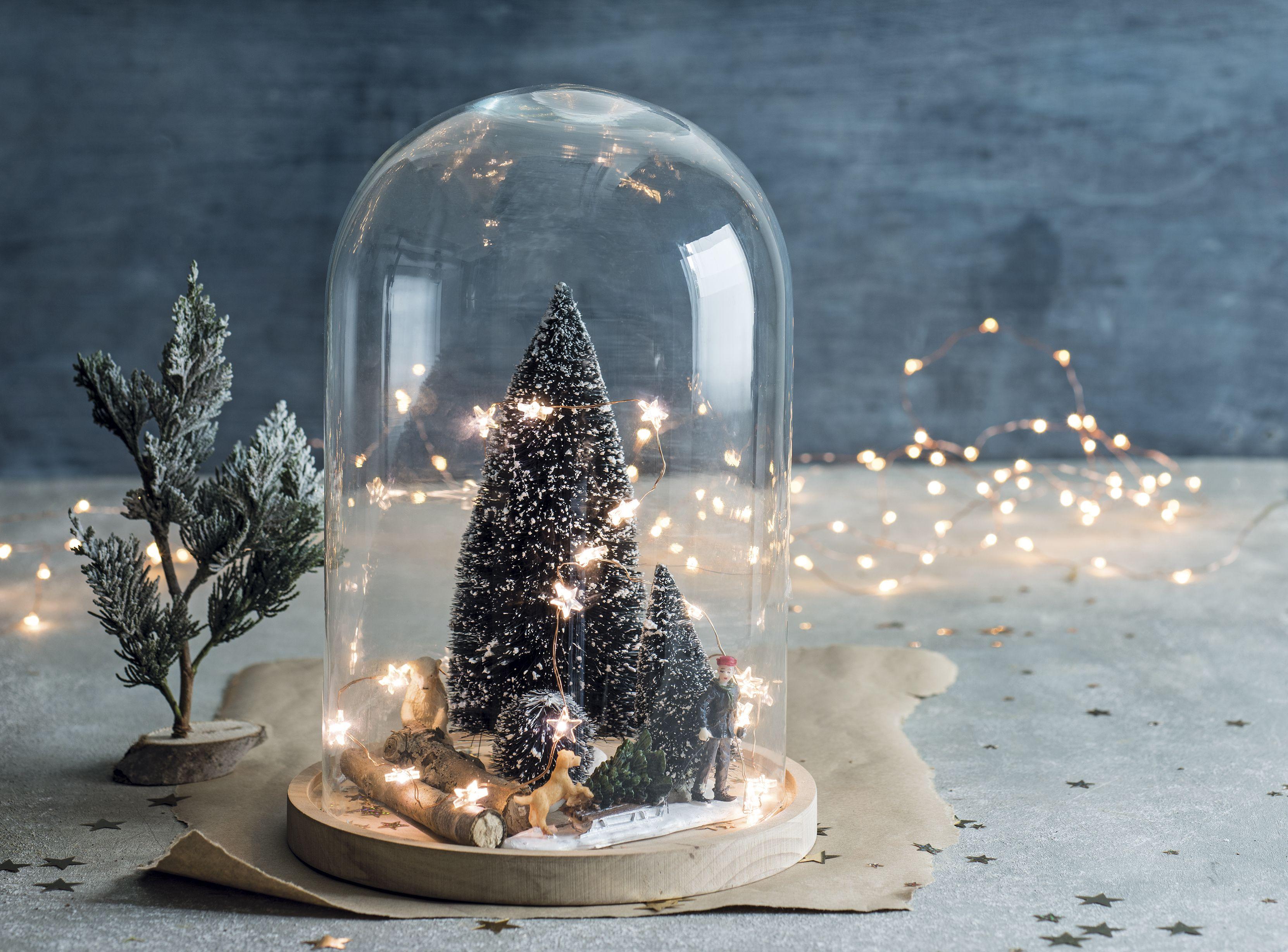 Versier een stolp met kerstboompjes en verlichting kers