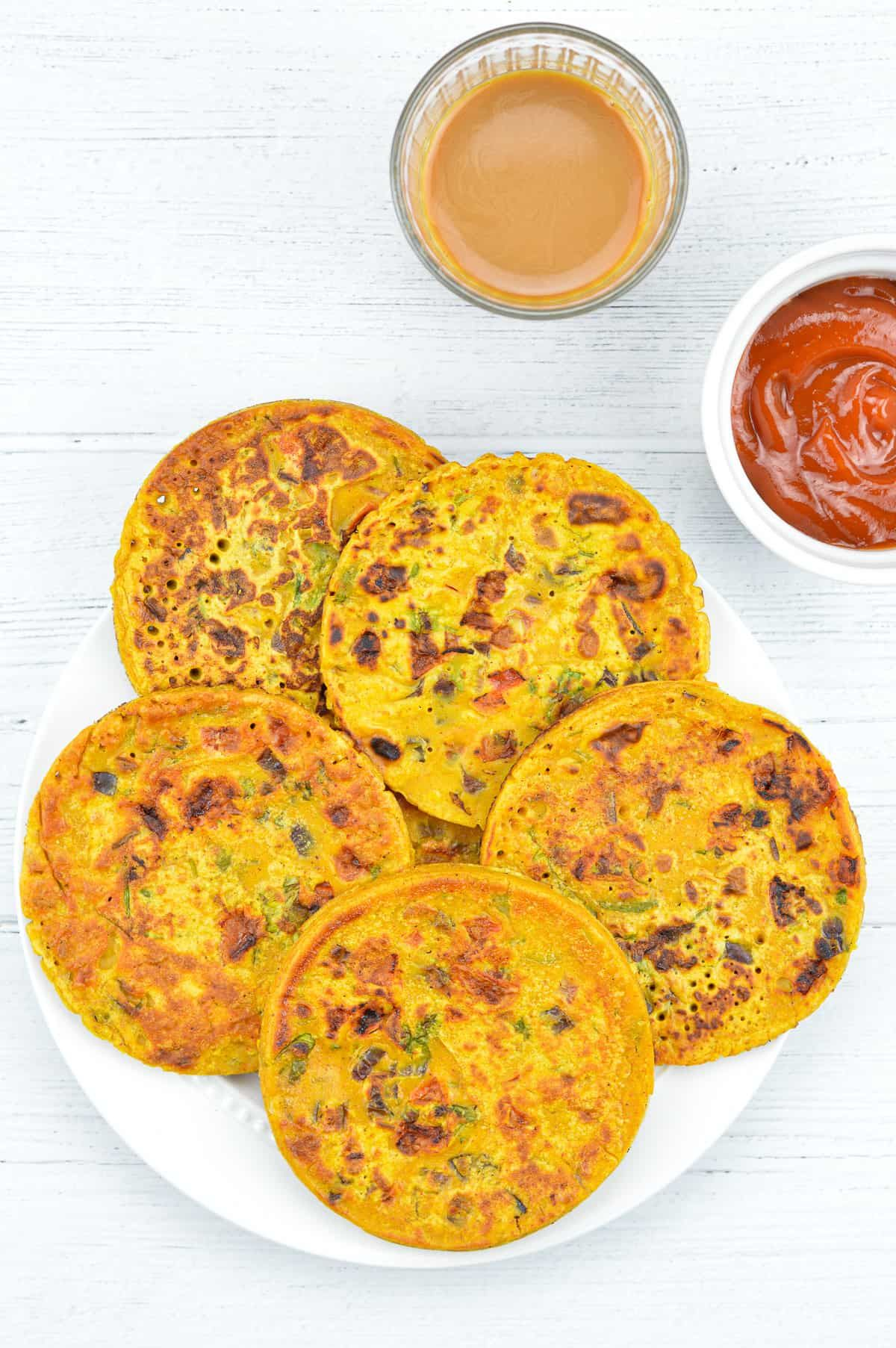 Besan Chilla / Indian Tomato Omelette - A quick and easy Indian breakfast recipe / tea time snack. Click over to know how to make healthy besan chilla, an Indian savory pancake that is naturally vegan and gluten free - with step by step photos and instructions. #besanchilla #tomatoomelette #indianbreakfast #indianbreakfastrecipes #indiansnacks #indianvegetarianrecipes