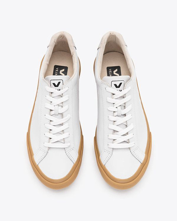 Elegant and minimal white leather low top sneakers with natural gum soles,  suede leather patch