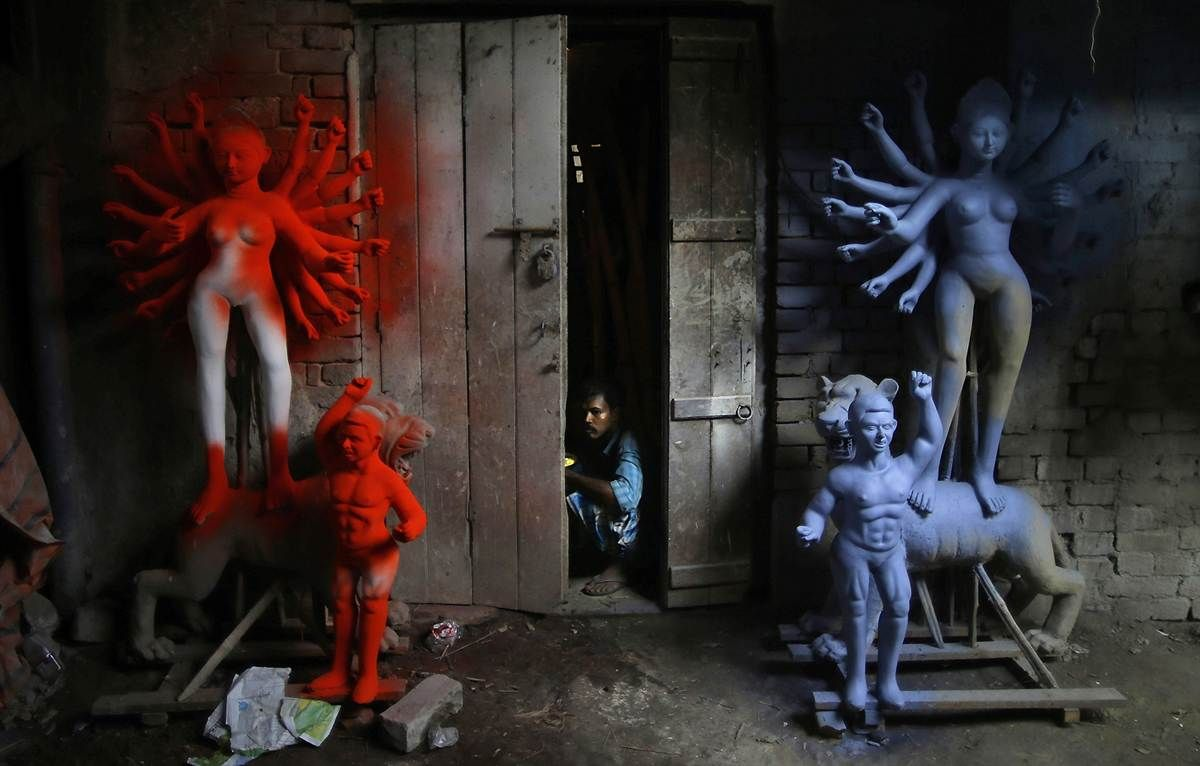 A laborer looks out of a workshop that prepares idols of Goddess Durga in Kolkata, India. Durga Puja, the festival dedicated to the worship of Goddess Durga, is celebrated from Oct. 20 to Oct. 24. Photo by Saurabh Das / AP