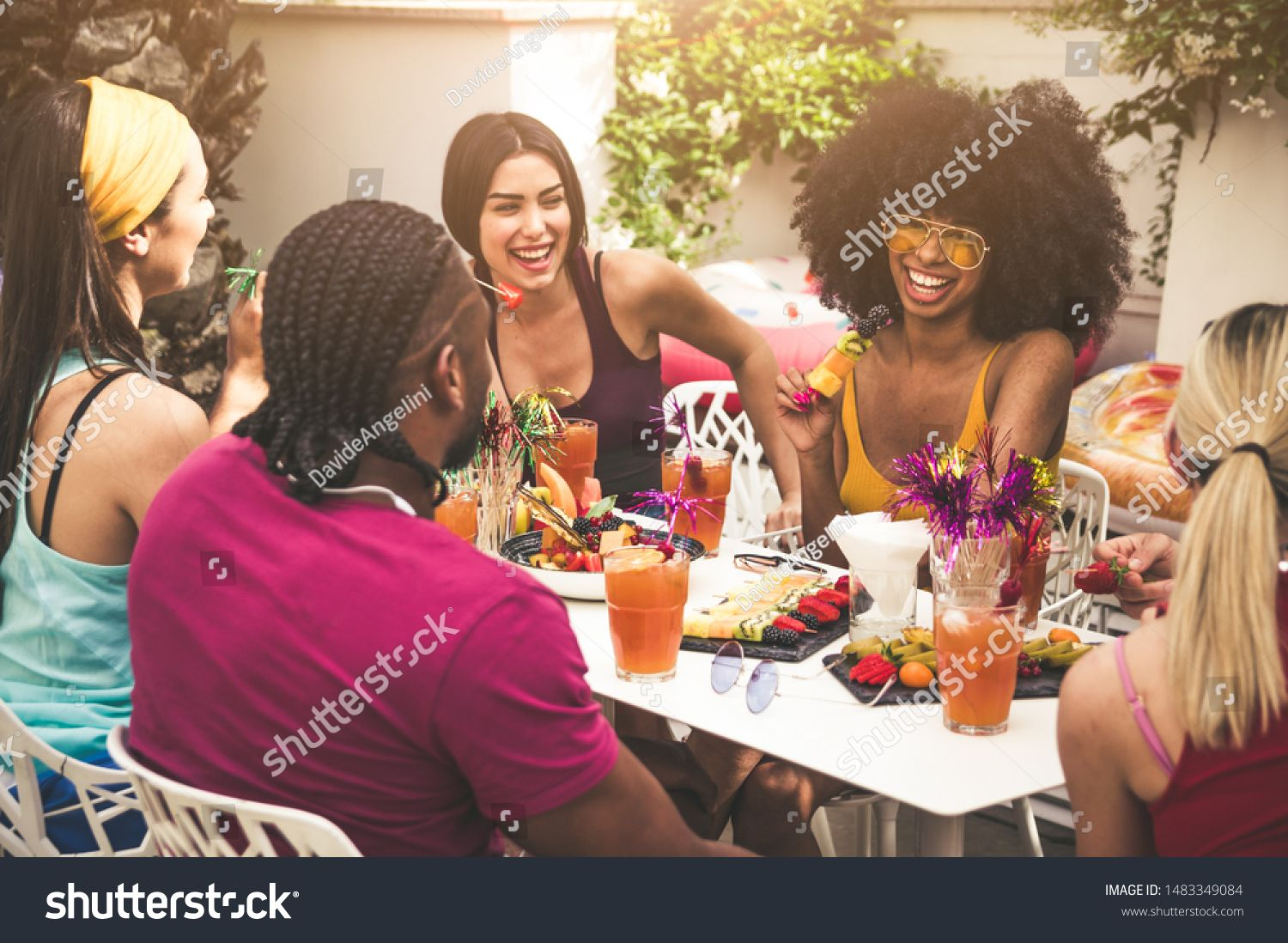 Group of friends enjoying meal and having fun outdoors  People talking and laughing togheter at the restaurant