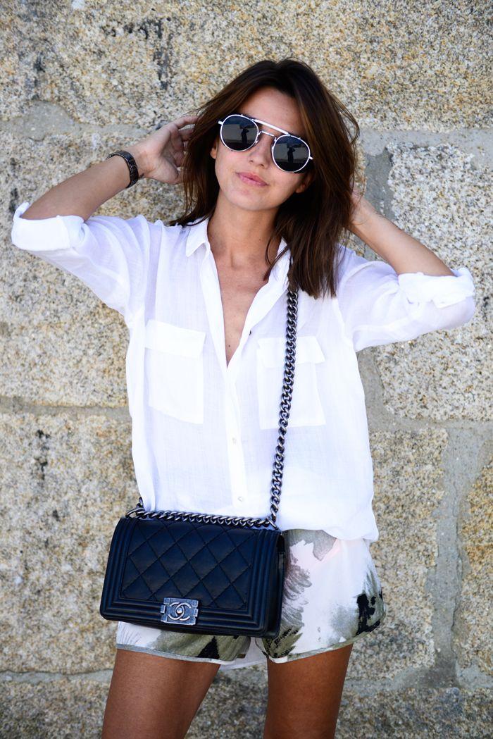 white shirt with big pockets, printed shorts, black Chanel boy bag and round sunglasses