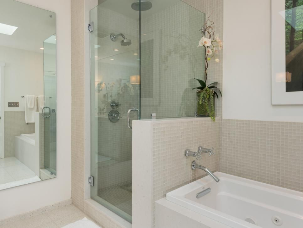 A master bathroom has glass shower doors that create the illusion of ...