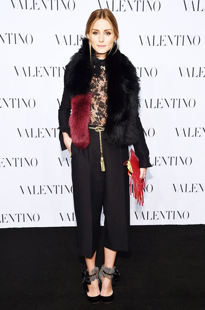 Olivia Palermo in a lace top tucked into black cropped trousers with a gold rope belt with tassel