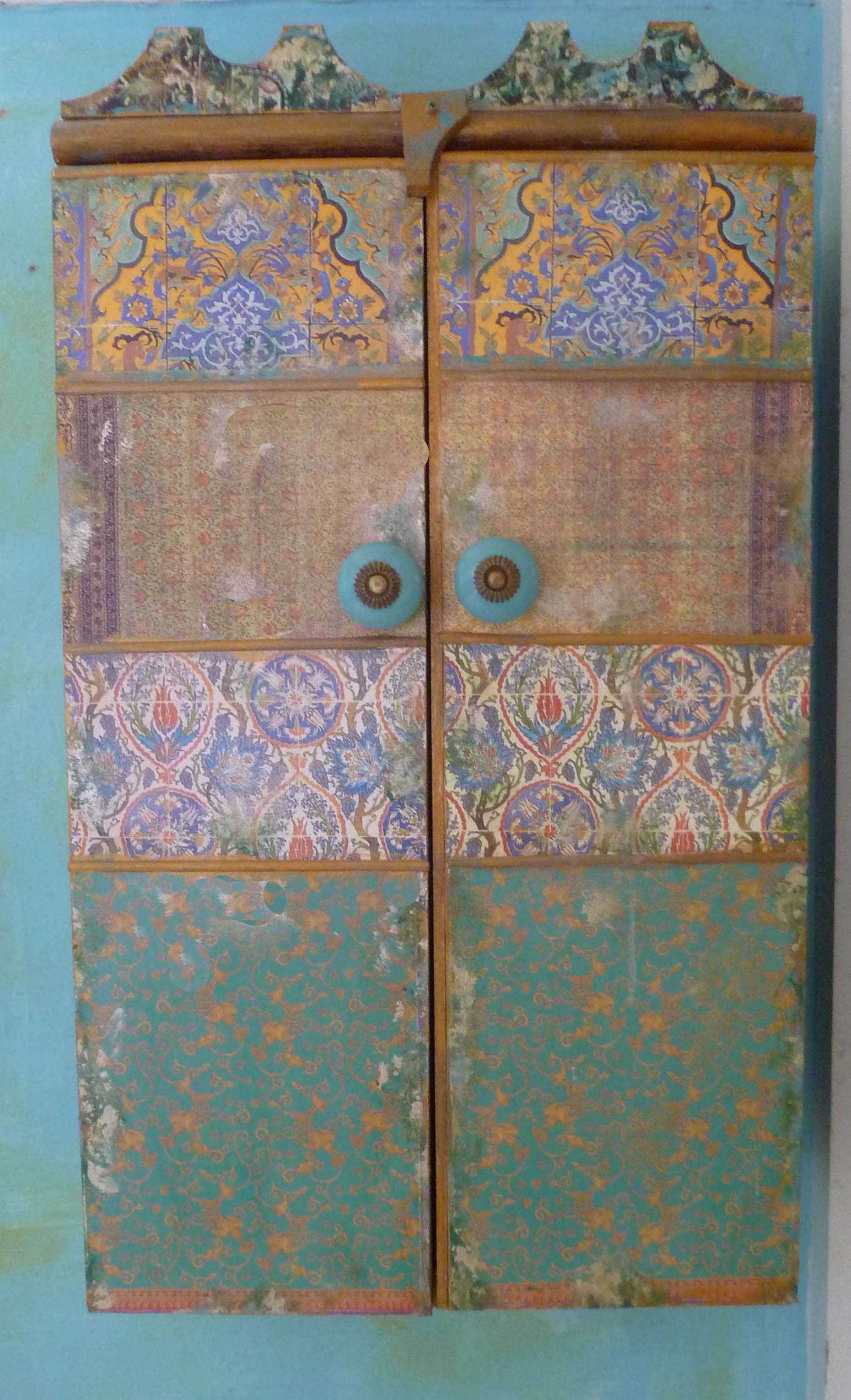Moroccan inspired cabinets are made in the decoupage technique, with many layers of varnish, distressed with acrylic paint.