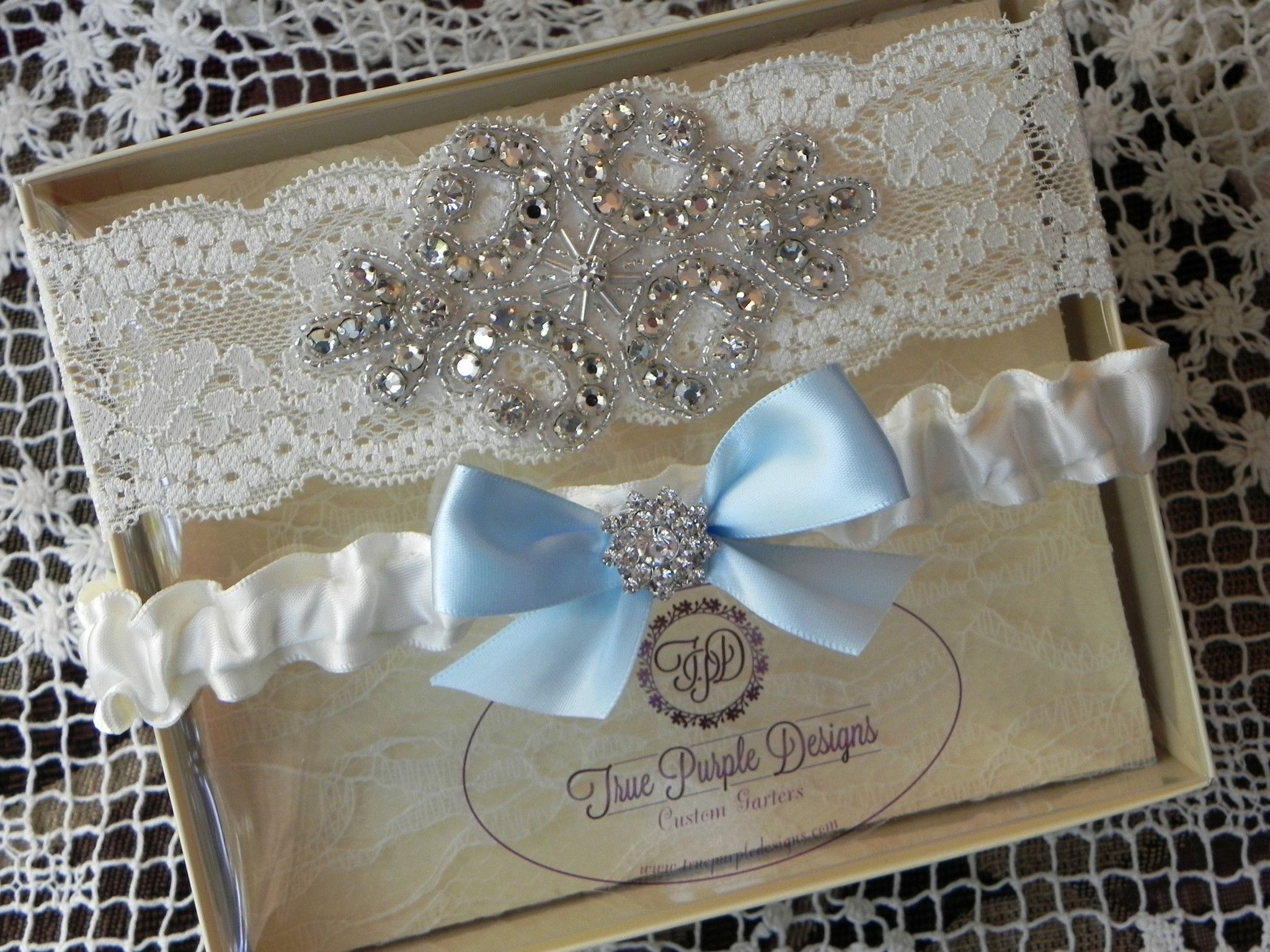 Ivory lace u satin rhinestone garter set with blue bow