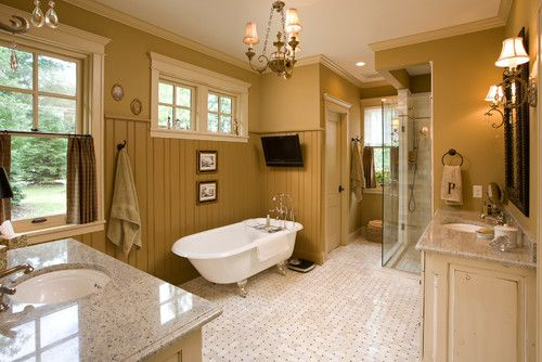 This master bathroom features mustard yellow walls that spread down the tall beadboard wainscoting that add a textured effect. Photo by Bob Michels Construction, Inc.