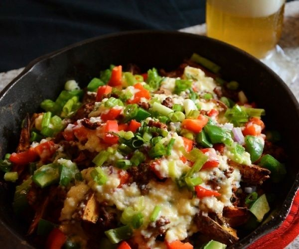 """Italian Sweet Potato """"Nachos"""" - Chicken sausage comes together with sweet potatoes, spicy peppers, and creamy gouda for a fun dish to cure any nacho craving."""