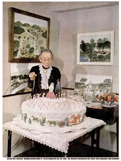Grandma Moses blows at the candles on her huge 88th birthday cake