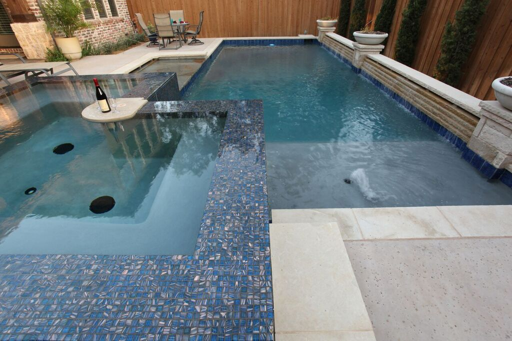 Classic pool design featuring mosaic tile surrounded spa, tanning ...
