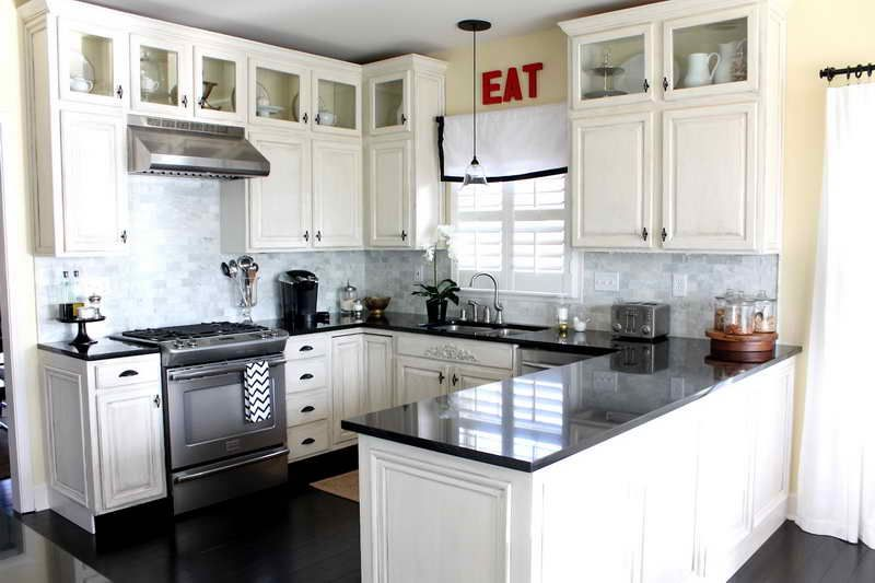 Off-white cabinets, grey marble backsplash, black counters, dark ...