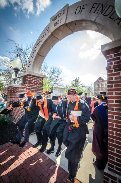 University of Findlay graduates jump through the Griffith Memorial Arch after undergraduate graduation ceremonies Saturday. Students traditi...