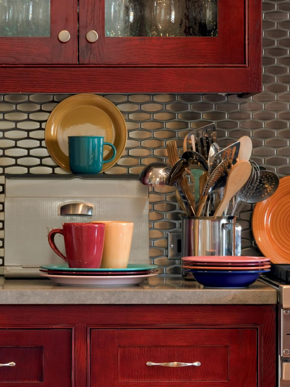 With This Metallic Kitchen Backsplash The Stainless Steel Tile Provides A Modern Contrast Against Multi Hued Fiestaware And Dark Red Cabinets