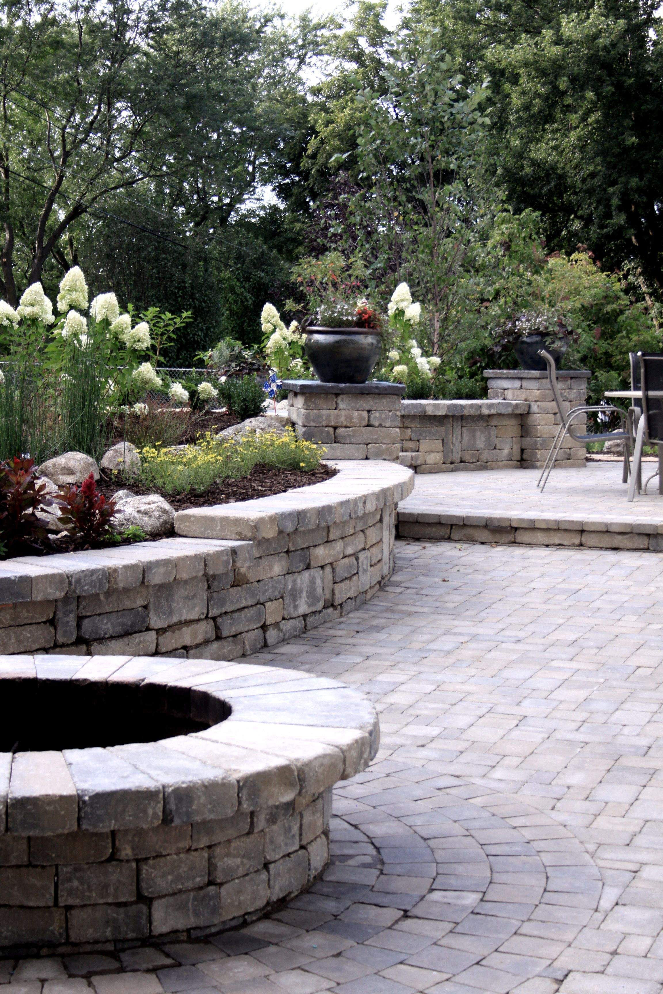 Multiple Outdoor Living Spaces Separated On A Split Level Stone Patio.  Stone Fire Pit Is Edged By A Matching Retaining Wall With Landscaping That  Doubles As ...