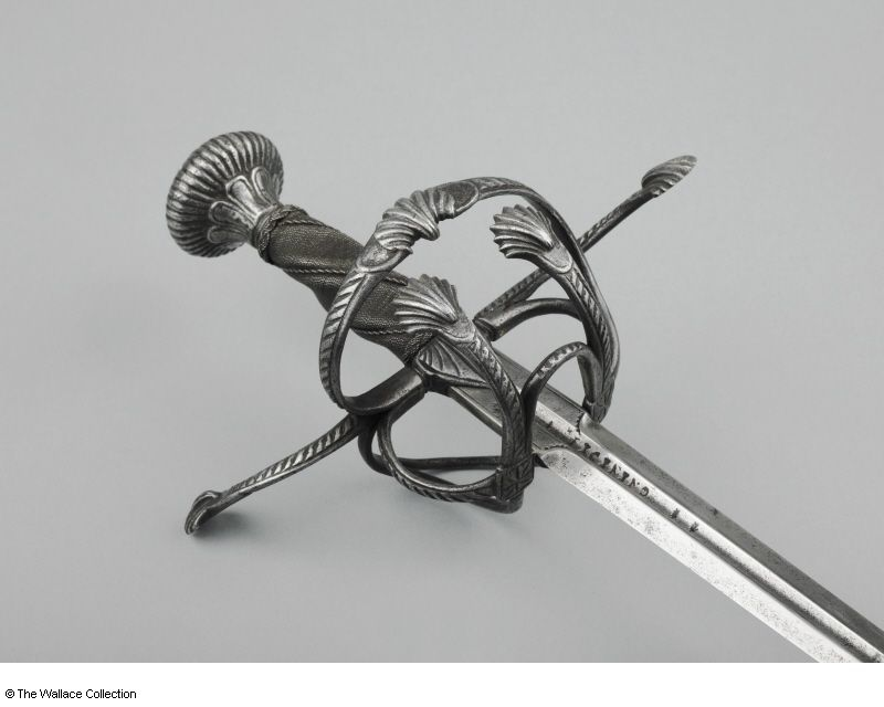 Rapier Possibly Antonio Piccinino (1509 - 1589) , Swordsmith Milan, Italy c. 1570 - c. 1630 (pommel) possibly c.1585 (guards) c. 1560 - 1589 (blade (Italian)) Iron or steel and blackened steel Length: 110.8 cm Width: 2.3 cm Weight: 1.07 kg Signature: '**ANTONIO** / ** PICININO**' Incised mark: Mound of three parts under a crown A540 European Armoury II