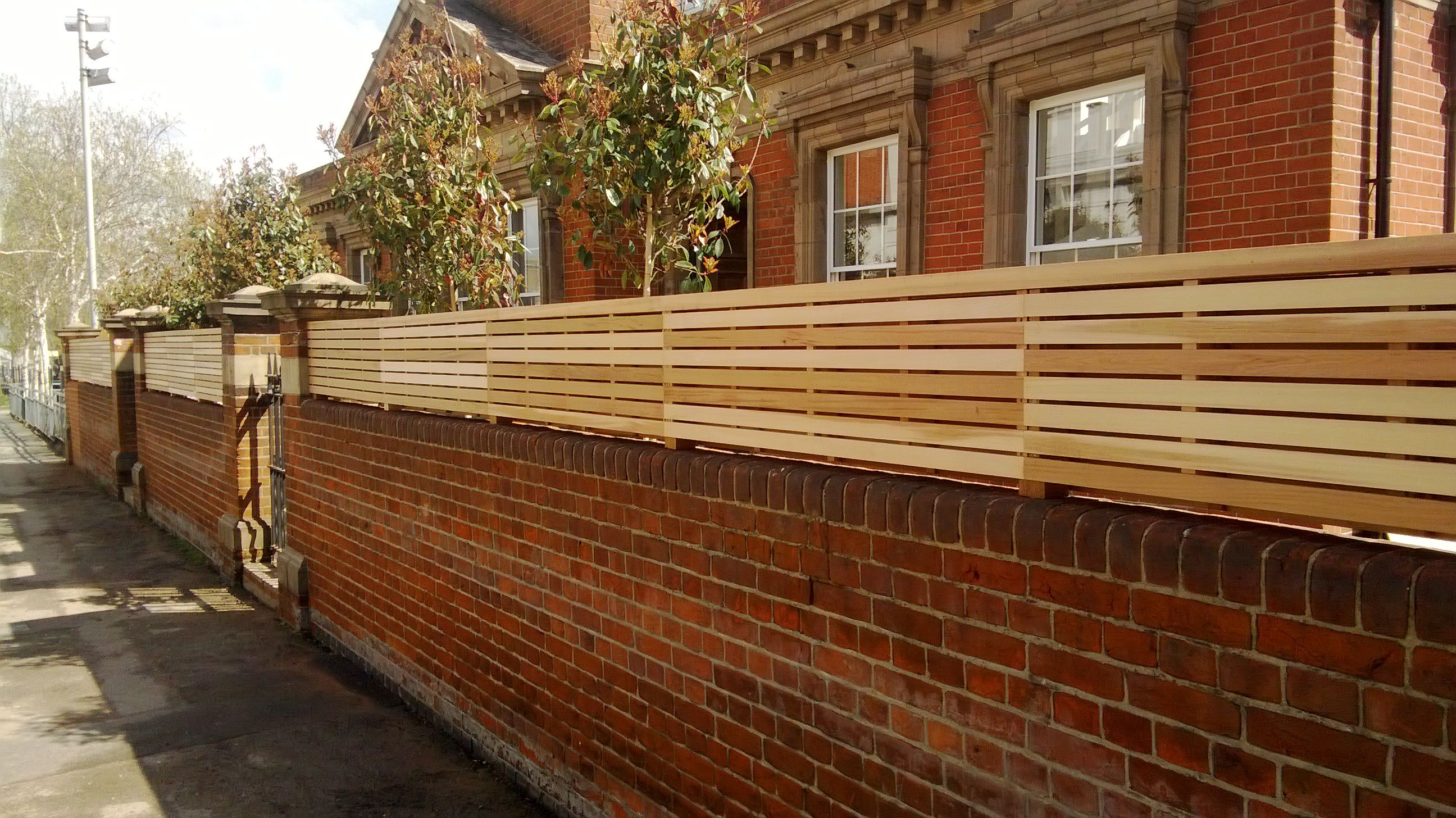 Slatted Panels Fixed To The Top Of A Wall Cedar Paneling Slatted Fence Panels Brick Fence