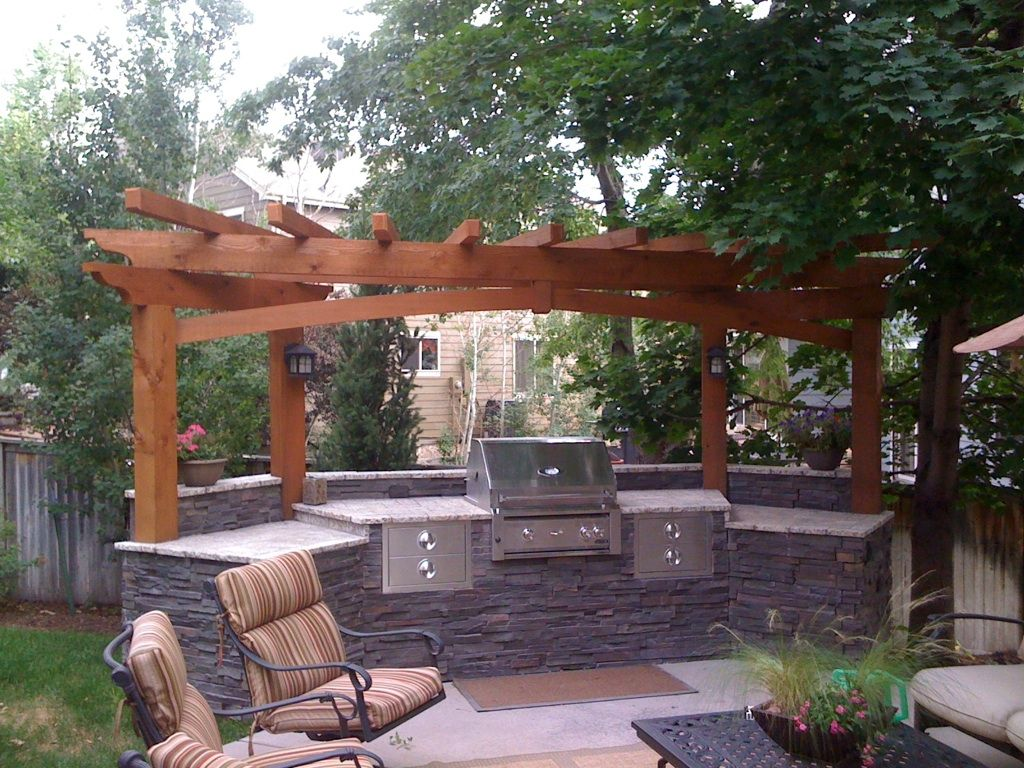 Custom outdoor kitchen with tumbled stone and gas grill hand crafted cedar pergola with accent for Outdoor kitchen designs with pergolas