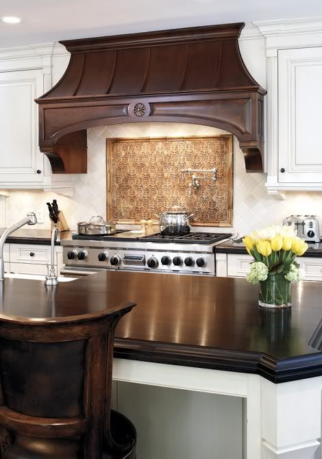 Wood Chimney Hoods ~ Kitchen with white cabinetry and dark wood detail