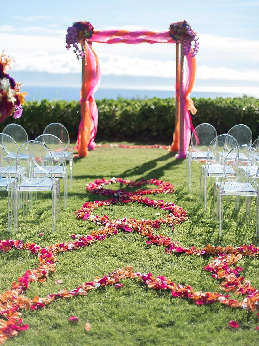 A bright orange and pink tulle wedding arch for an outdoor wedding