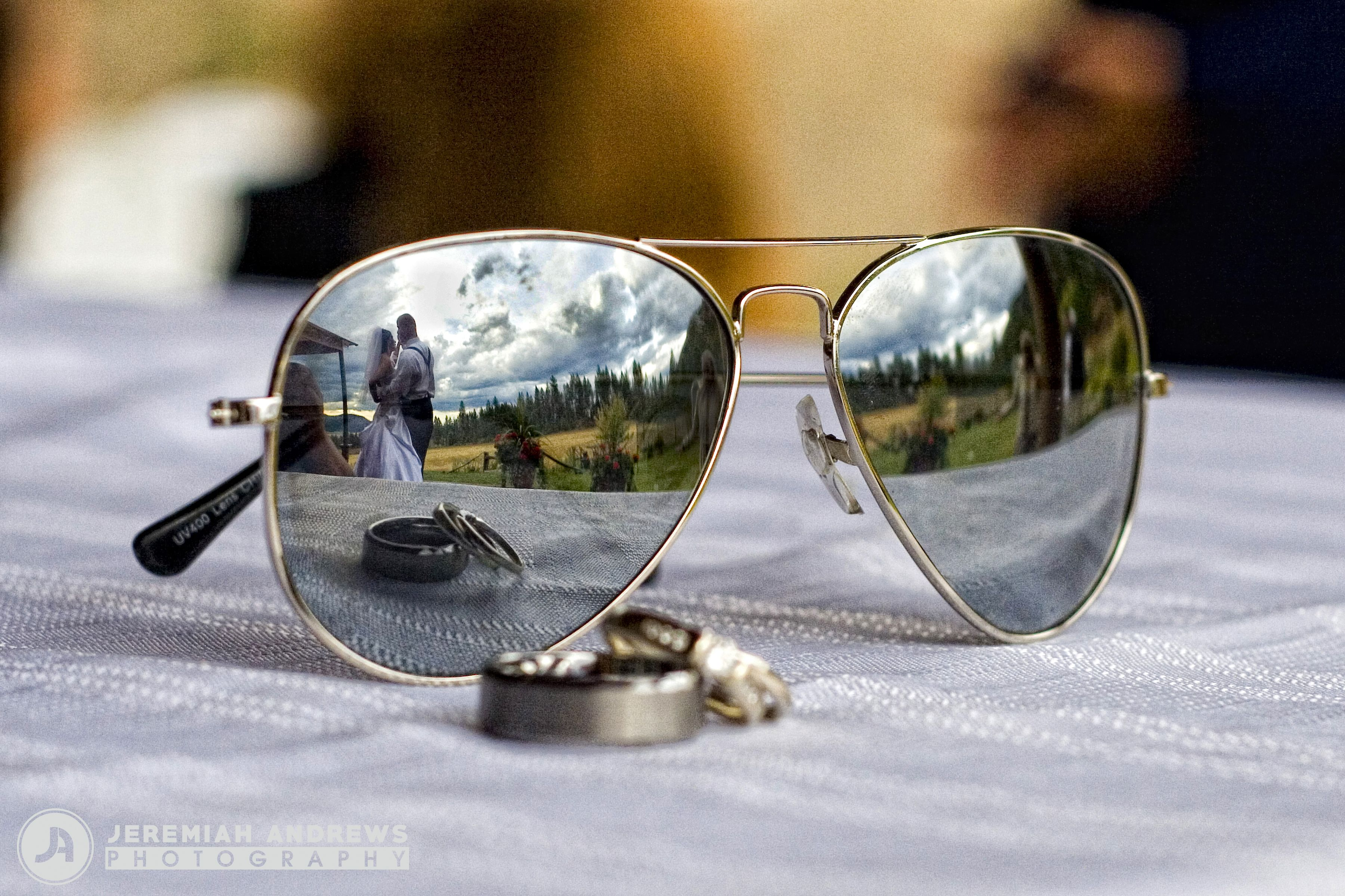 Wedding rings and couple reflected in aviator sunglasses