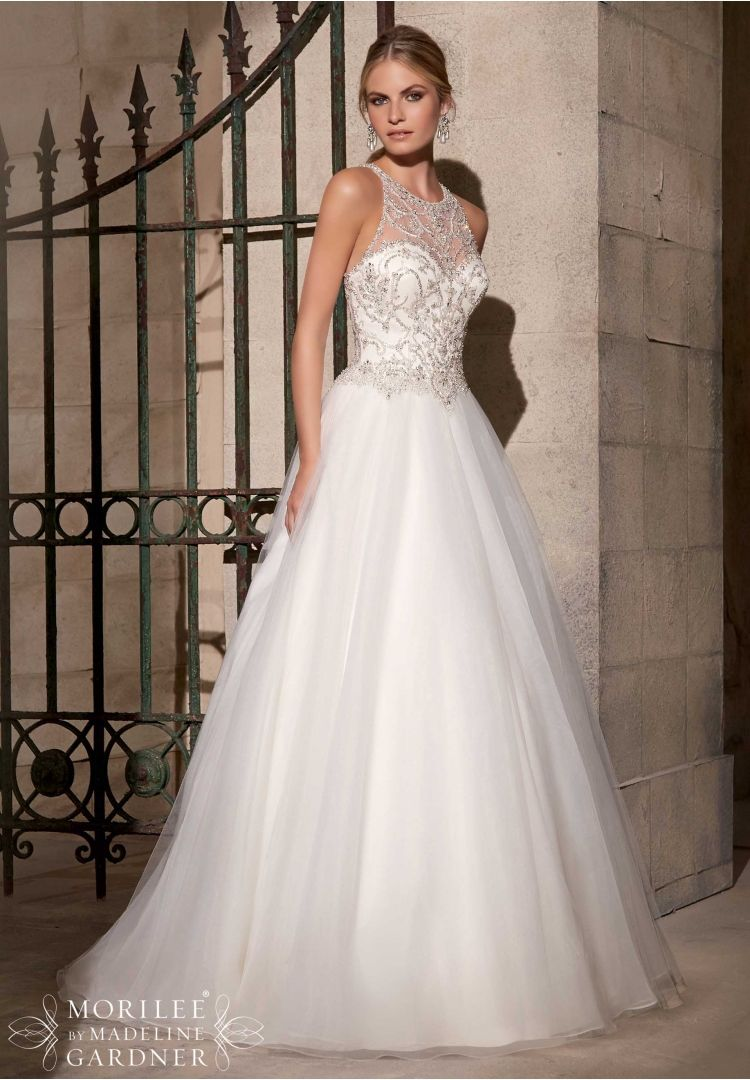 Wedding Dresses and Wedding Gowns by Morilee featuring Crystal Beaded Embroidery on a Tulle Ball Gown Ornate beadwork, and a high neckline give this tulle ballgown a truly unique look. The illusion back is accented by intricate beading and covered buttons. Available in White/Silver, Ivory/Silver