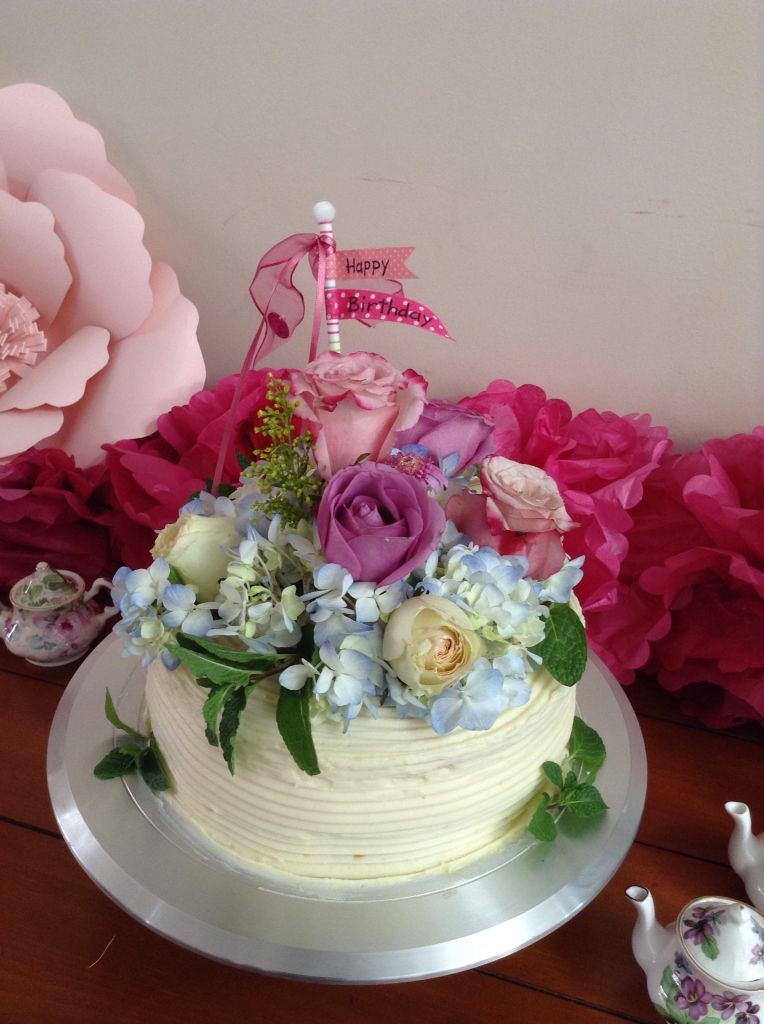 Birthday cake with fresh flowers topper.