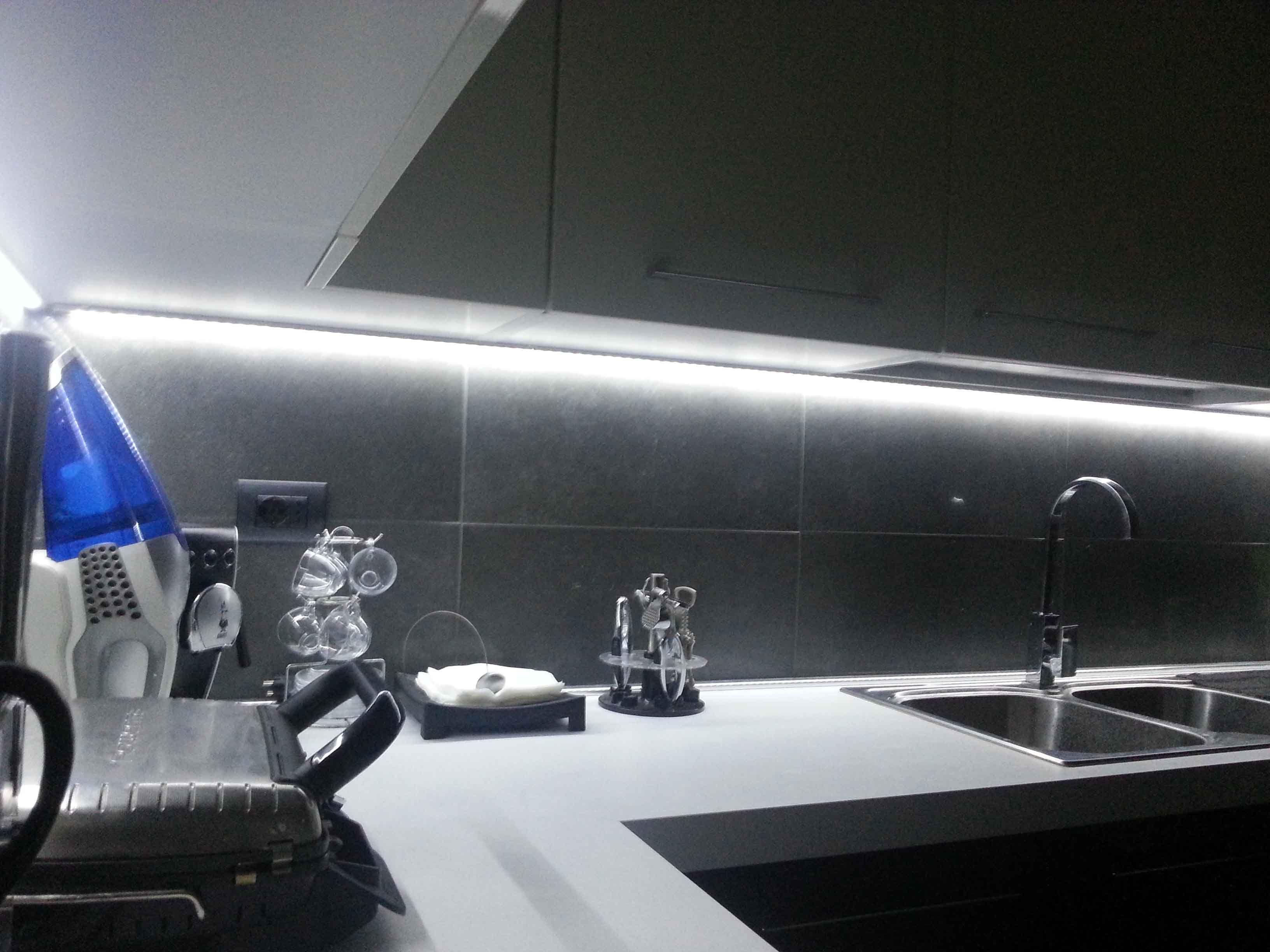 il piano di una cucina illuminato da una striscia led bianca