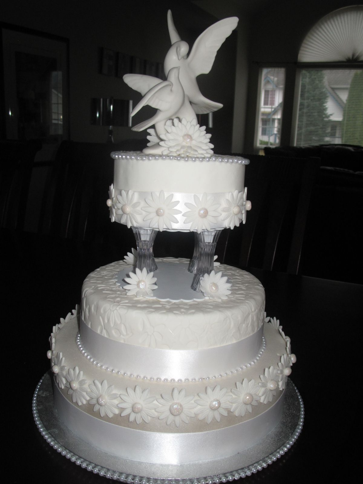 This is a three tiered wedding cake that has been adorned with white