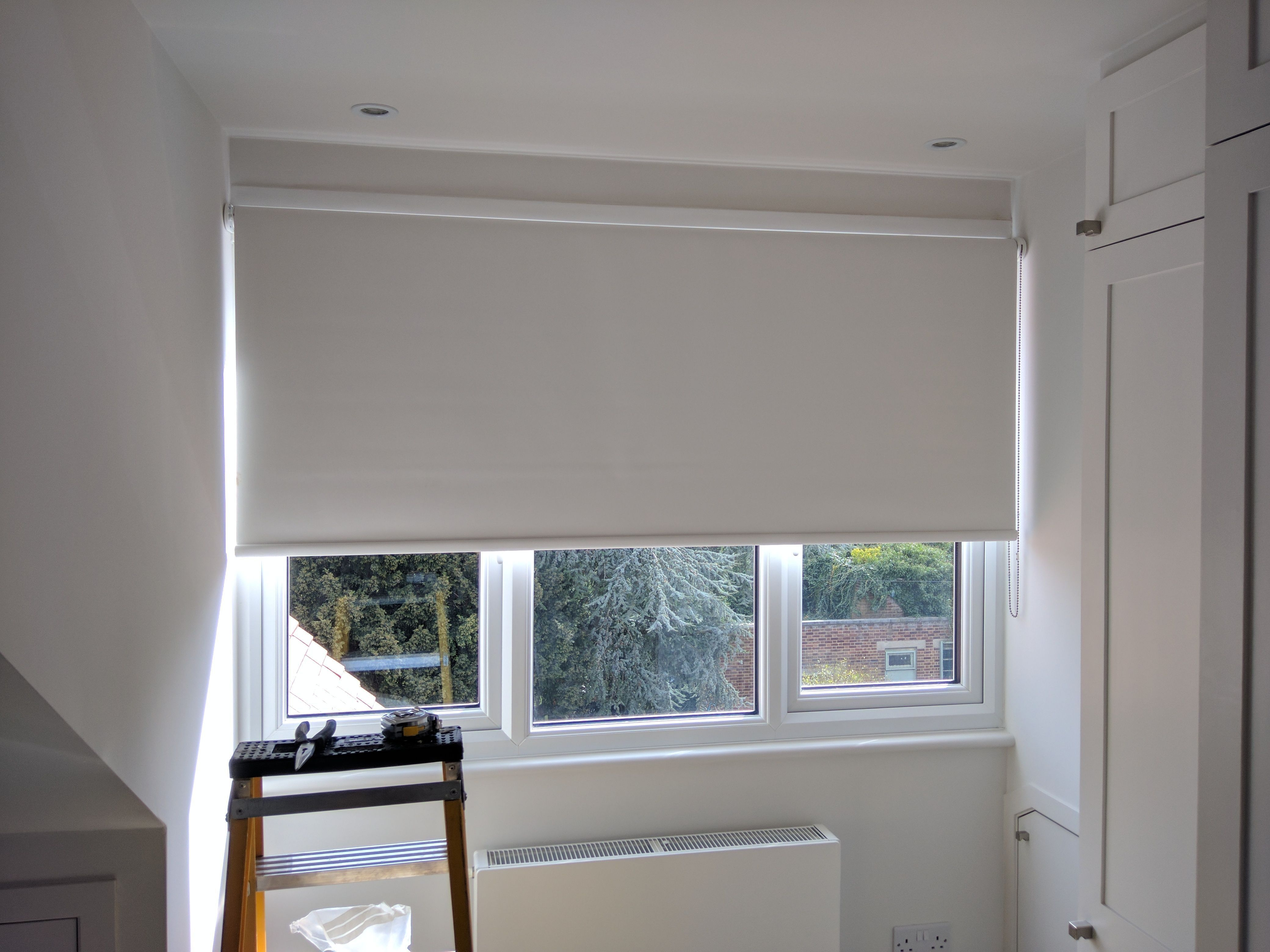 Window coverings shutters  blackout roller blind in polar white colour fitted to bedroom window