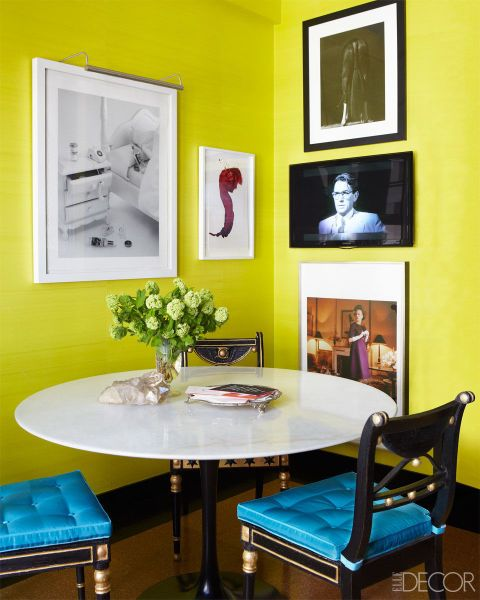 Regency chairs with silk cushions surround a Saarinen table tucked away in a cheery corner of the kitchen; the walls are lined with vintage silk paper, the artworks are by, from left, Rachel Lee Hovnanian, James Nares, Steven Klein (top), and Mark Shaw, and the television is by Samsung. Tour the rest of the home here.
