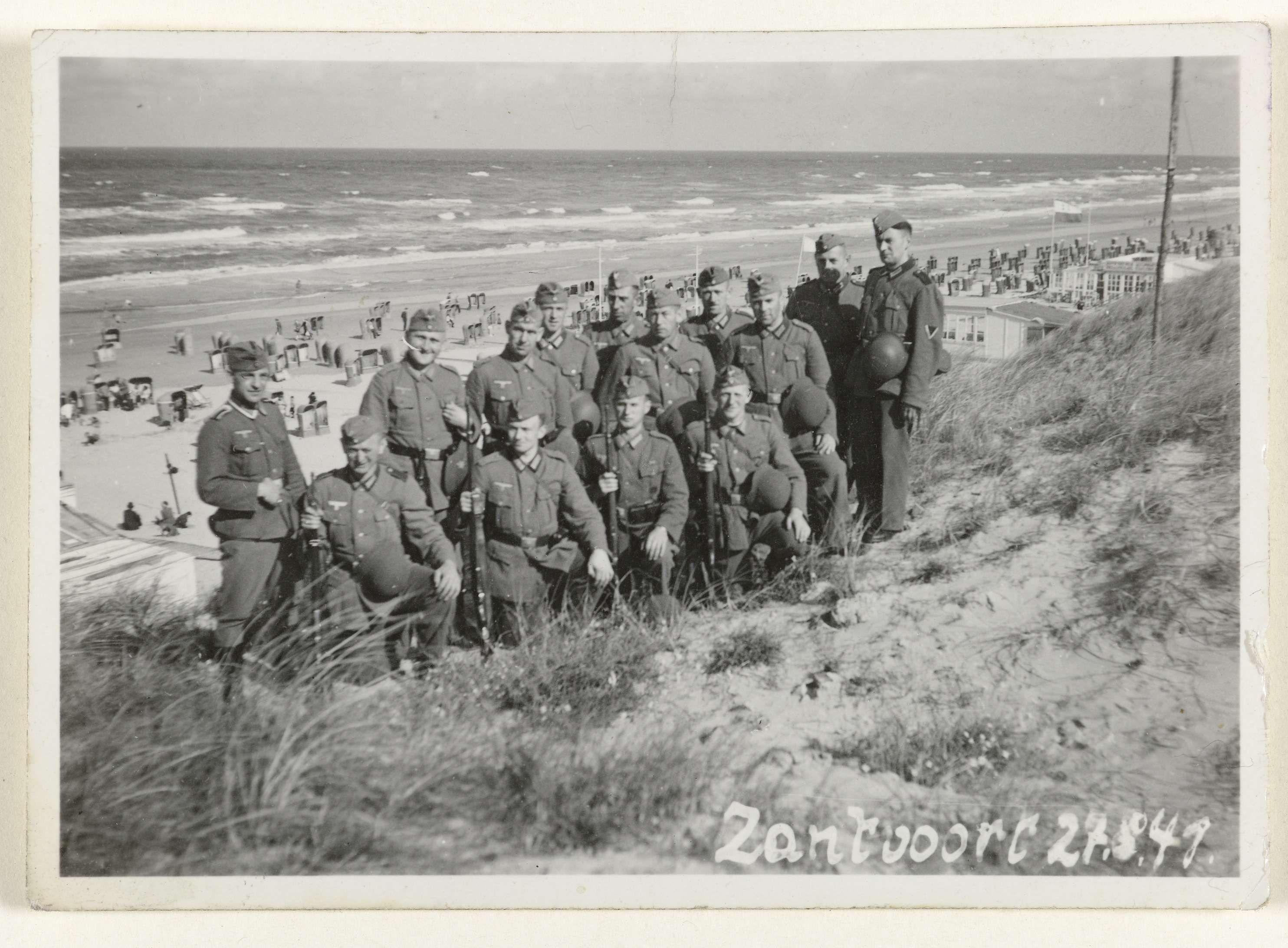 Anonymous | Duitse soldaten in Zandvoort, 1941, Anonymous, 1941 | Amateurfoto van Duitse soldaten uit 1941 in Zandvoort. Ze staan in uniform in de duinen, het strand achter hen is vol met badgasten.