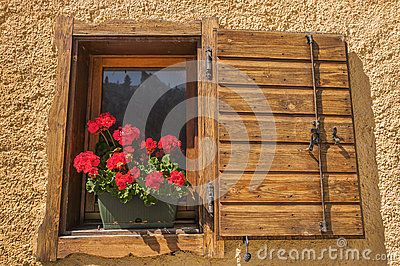 Alpine Window With A Wooden Shutter And Geranium Flower