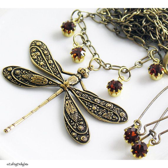 """This lovely necklace has a large antique brass dragonfly, accented with dark amber Swarovski rhinestones on an antique brass chain with lobster clasp.   Necklace length is 24"""".   Earrings are the same dark amber Swarovski rhinestones on long kidney wires 2.5"""".  An homage to my favorite author, Diana Gabaldon and her Outlander series of novels. The second book title is """"Dragonfly in Amber"""".   """"He had been fixed in my memory for so long, glowing but static, like an dragonfly frozen in…"""