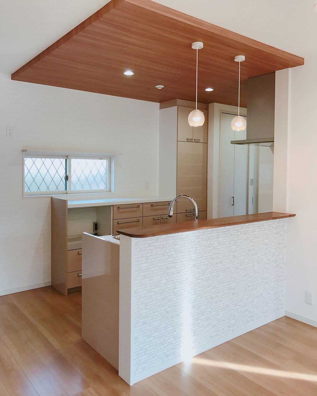 木目ブラウンとレンガ調ホワイトの優しいキッチン キッチンスペースの