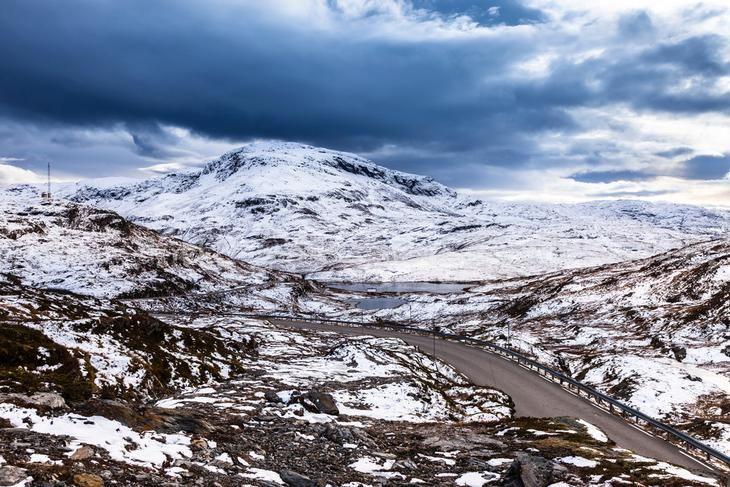 ROAD RUNNING THROUGH A SNOW COVERED WINTER LANDSCAPE IN VIKAFJELLET, SOGN OG FJORDANE, NORWAY.