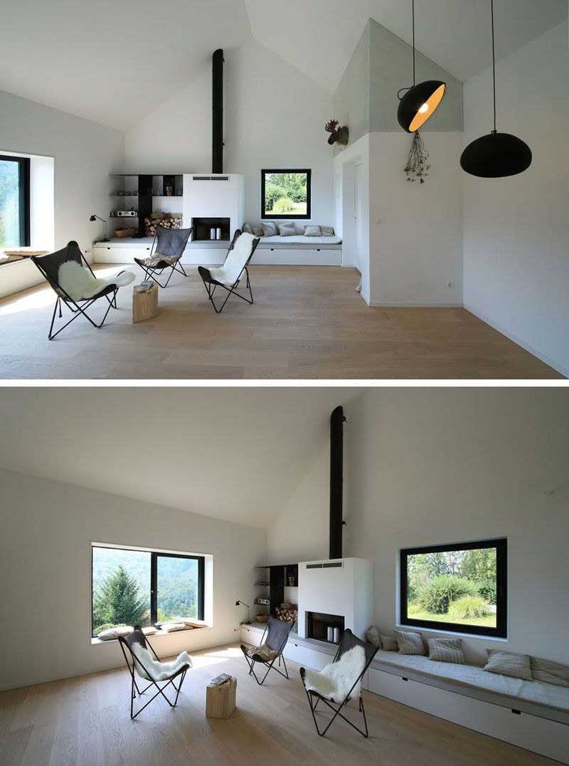 In this minimalist living room, built-in window seats and storage are positioned either side of the fireplace.