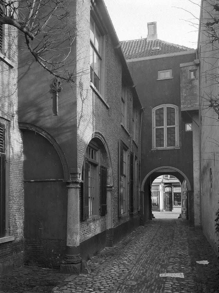 Breda. Ginnekenstraat, zijgevel van woonhuis met gesloten zuilengang en zicht op poortgebouw. 1913.