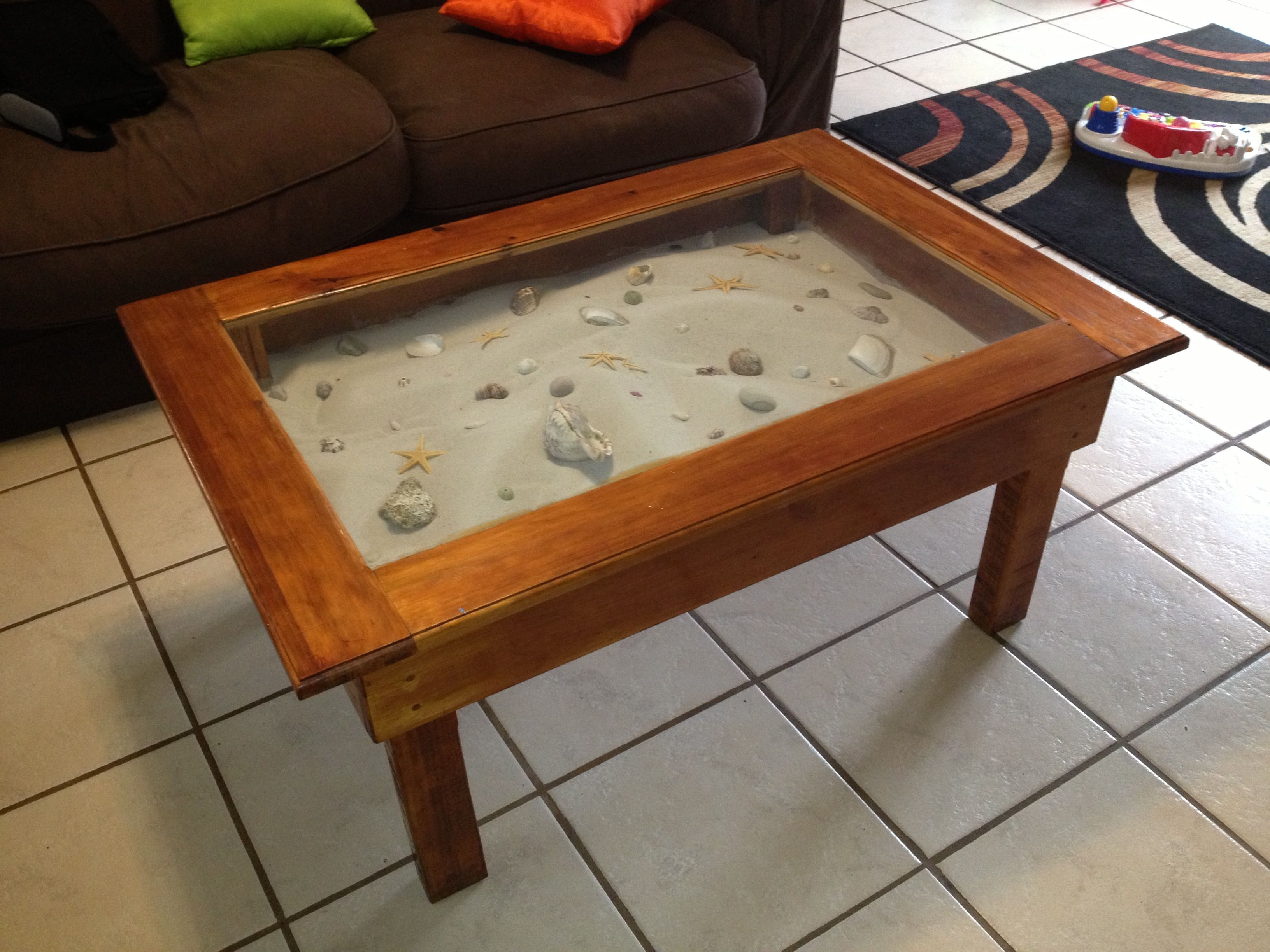 A coffee table display cabinet filled with sea sand and shells