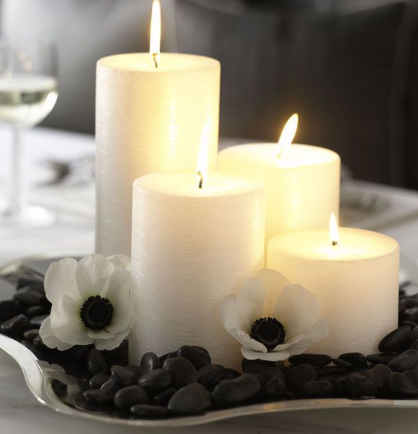 simple centerpiece of river stones, shimmering pillar candles, and french anemones--the black center of the blossom is tres chic