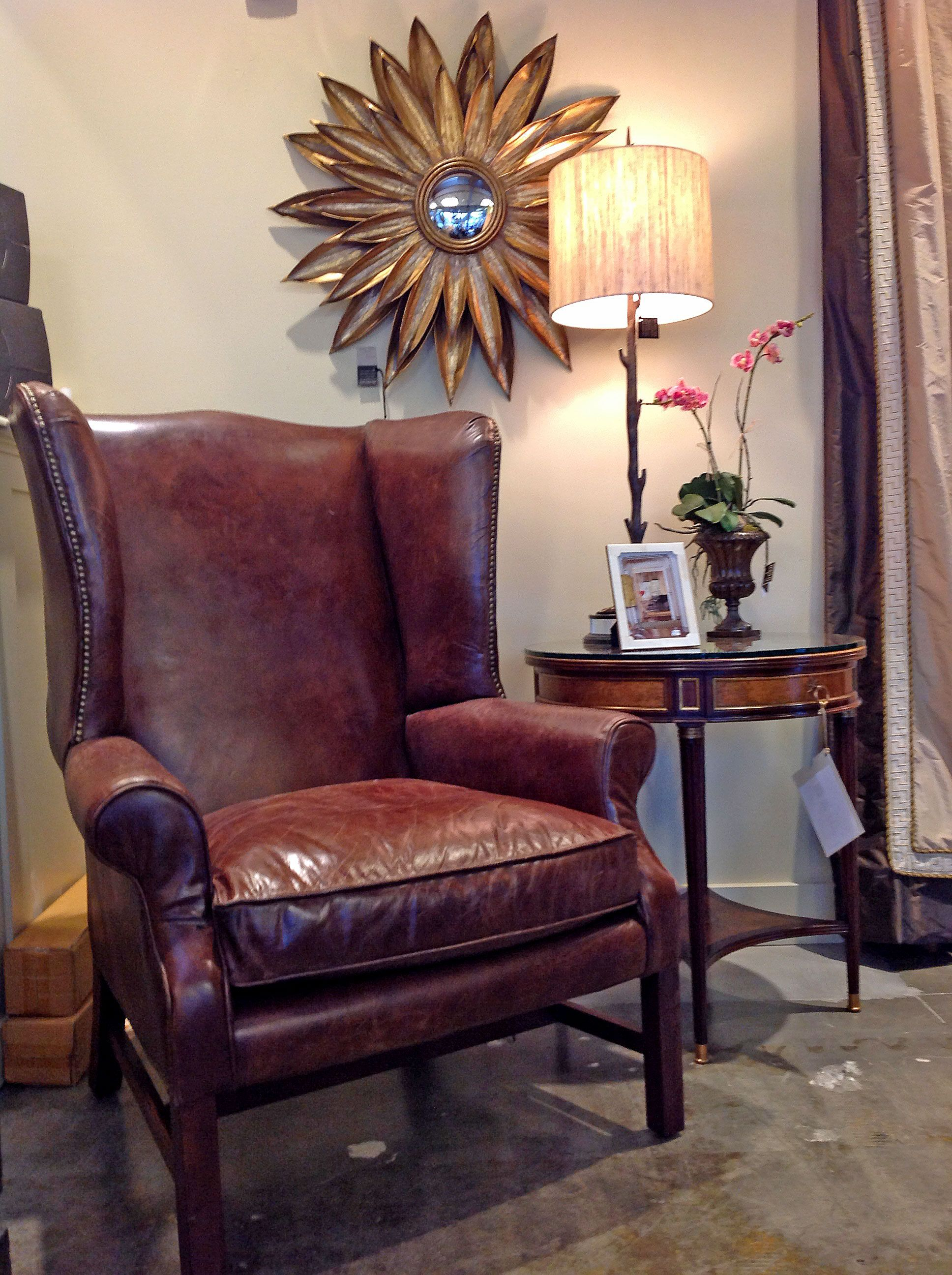 Leather wing chair arranged with small round side table and lamp leather wing chair arranged with small round side table and lamp gold trimmed round sunburst geotapseo Choice Image