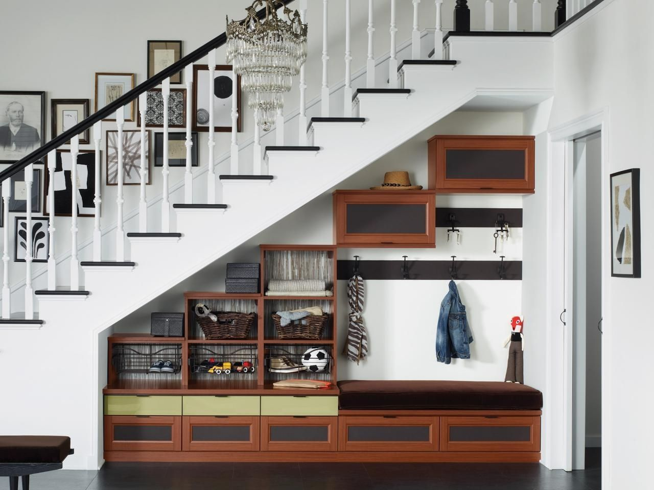 Adding cubbies shelving or hanging space under a staircase provides storage in an otherwise unused space and creates a designated spot for rain boots