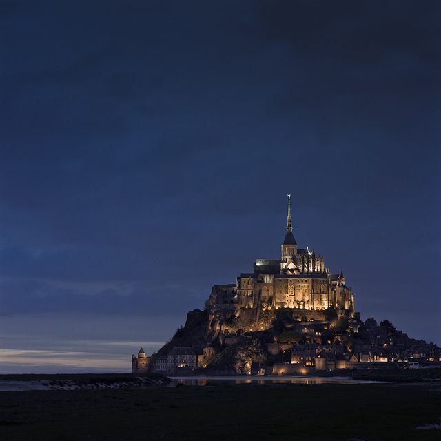 mont saint michel fully lit for the night, as the sunset fades in the west. by thetzar, via Flickr
